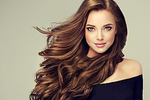 a headshot of a brunette woman using luxury Russian hair extensions