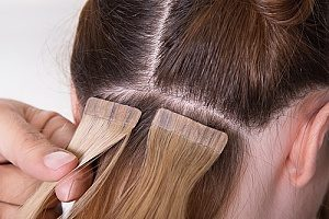 clip in hair extensions that a woman is installing