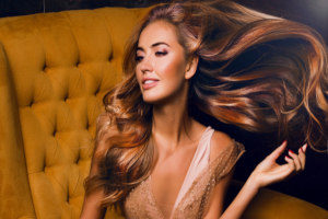 a beautiful woman sitting in a chair and flipping her hair that has hair extensions put in