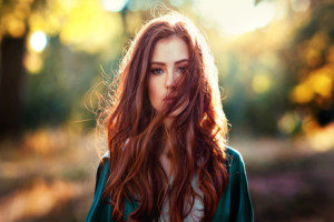 beautiful redheaded woman with hair extensions wearing a green dress