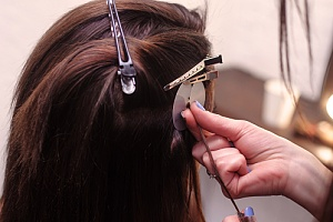woman sectioning her hair for clip-in hair extensions to be put in