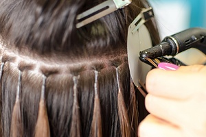 a woman receiving hot fusion hair extensions